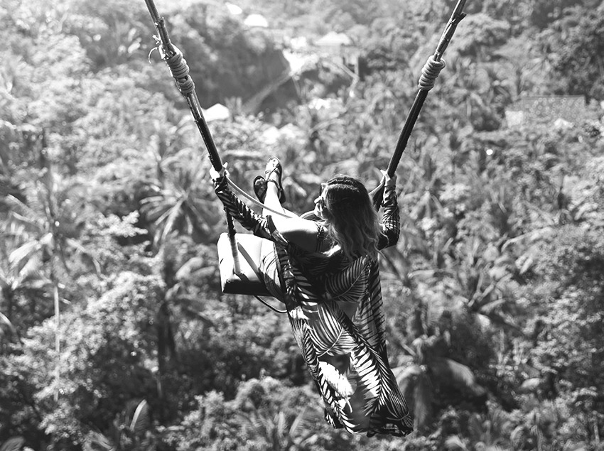 women on swing in bali black and white